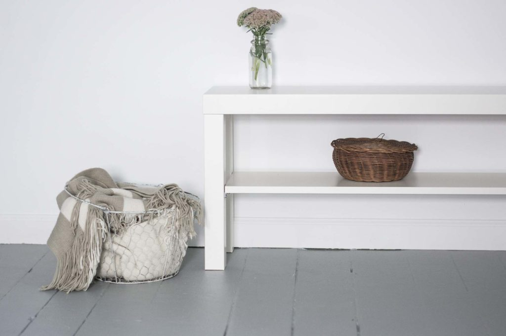 minimal shelving with baskets and flowers in vase